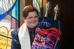 Boy with Torah at Bar Mitzvah in front of stained glass in San Diego CA